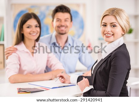 Attractive travel agent showing catalog with tours to happy young couple. - stock photo