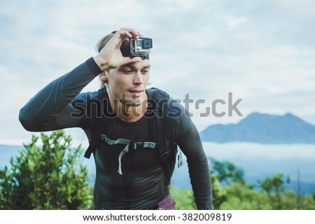 Attractive Traveler with Go PrO camera on his hand against the Batur volcano from Kintamani, Bali, Indonesia