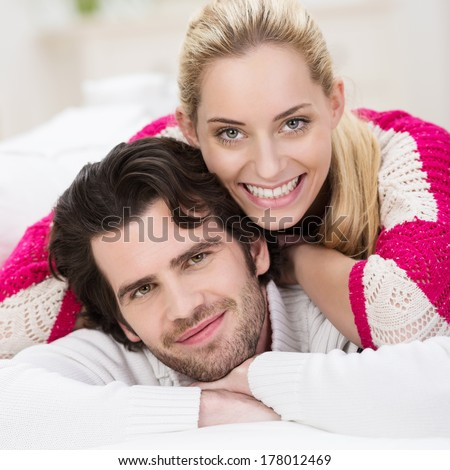 Attractive trendy young couple smiling into the camera as they pose with their heads close together, closeup facial portrait - stock photo