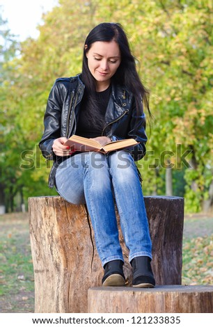 Attractive trendy young woman sitting on a tree stump reading a book while enjoying the sunshine outdoors - stock photo