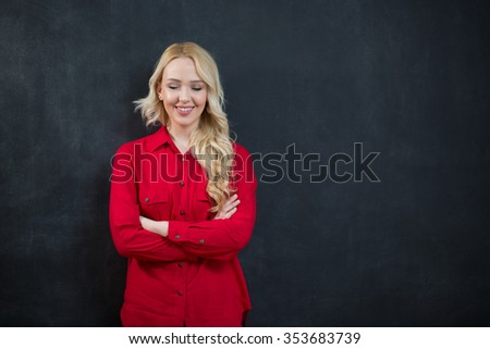 Attractive trendy young woman with a contemplative expression standing against a dark background staring pensively into the air, with copyspace - stock photo