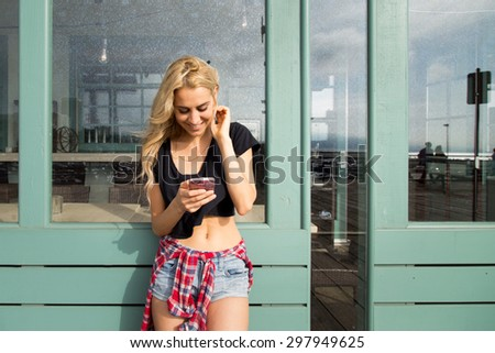 Attractive twenty-something woman texts on her mobile phone. She is smiling and happy, She  looks like a California Beach girl. She is outside on a summer day on a boardwalk. - stock photo