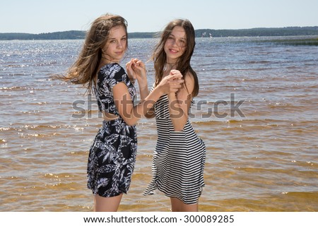 Attractive twins sisters. Close up of two beautiful smiling young women standing together