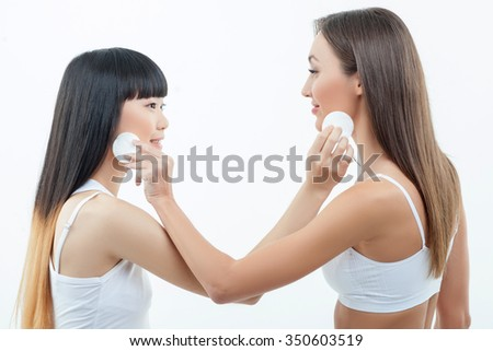 Attractive two slim women are caring of their skin. They are standing and touching sponge to each other faces. The Caucasian and Asian ladies are smiling. Isolated on background - stock photo