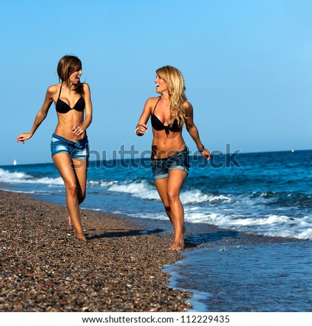 Attractive two young girl friends running along seaside..