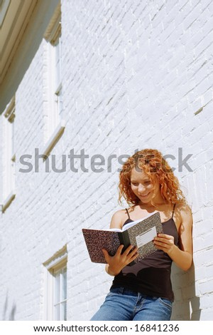 Attractive urban girl against white brick wall.