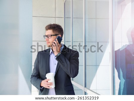 attractive urban young businessman with phone device and coffee in hands on office building background - stock photo
