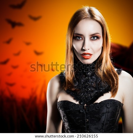 attractive vampire in front of a halloween background - stock photo