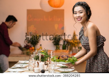 Attractive Vietnamese woman putting plate with fried chicken on dinner table