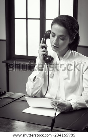 Attractive vintage secretary working at desk and having a phone call