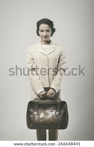 Attractive vintage woman smiling and holding briefcase
