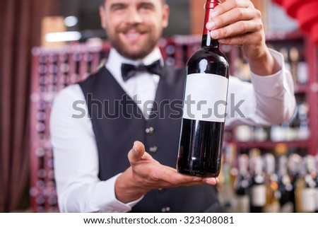 Attractive waiter is holding a bottle of wine and showing it to camera. He is standing and smiling in wine-cellar. Focus on his hands with bottle - stock photo