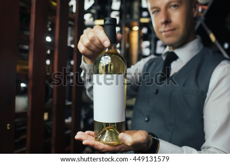 Attractive waiter is holding a bottle of wine and showing it to camera. He is standing and smiling in wine-cellar. Focus on his hands with bottle