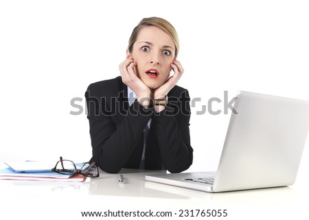 attractive white blond businesswoman sitting at office desk working with laptop in stress looking upset and dealing work issues in panic and fear face expression - stock photo