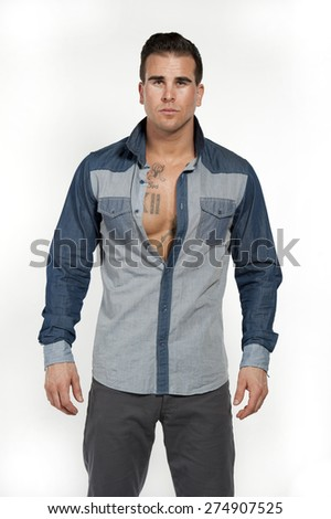 Attractive white caucasian male model wearing a jean shirt and gray pants posing in a studio on a white background while looking at the camera. - stock photo