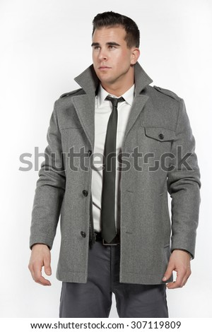 Attractive white male wearing a fitted white shirt and gray pants with a black belt and gray jacket while posing in a studio setting on a white background and looking at looking to the left. - stock photo