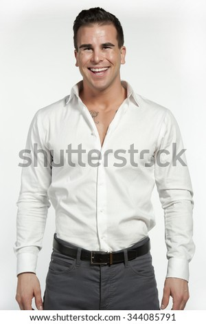 Attractive white male wearing a fitted white shirt and gray pants with a black belt while posing in a studio setting on a white background and looking at the camera and smiling.