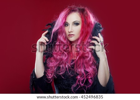 Attractive witch with red hair performs magic on a pink background. Halloween, horror theme. - stock photo