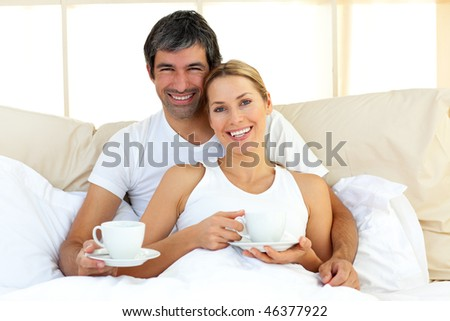 Attractive woman and her boyfriend drinking coffee lying in the bed - stock photo