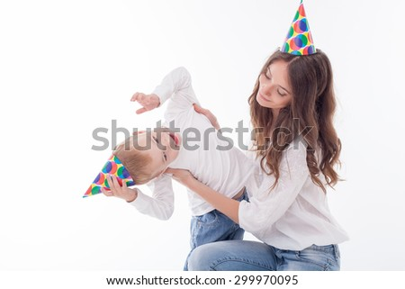 Attractive woman and her son are celebrating birthday. They are wearing holiday cap and smiling. She is embracing the boy playfully. Isolated on background - stock photo