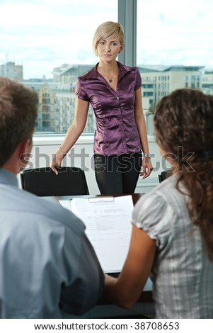 Attractive woman applicant arriving to job interview. Over the shoulder view. - stock photo