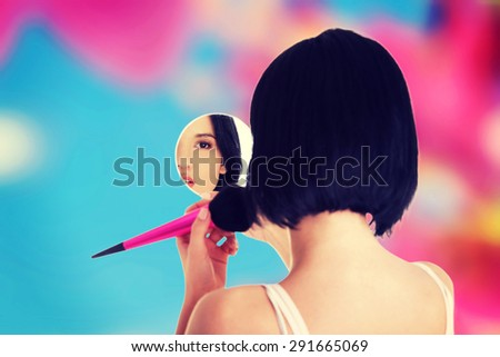 Attractive woman applying make up - stock photo