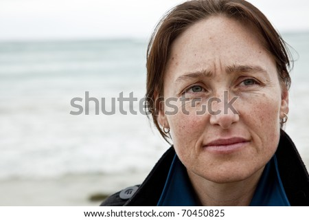 Attractive woman at beach with thoughtful expression. - stock photo