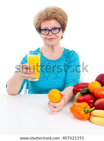 Attractive woman at the age drinking orange juice and holding an orange in her hand, isolated on white background - stock photo