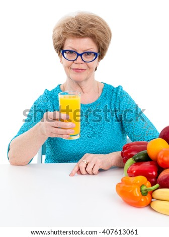 Attractive woman at the age offering orange juice in her hand, isolated on white background - stock photo