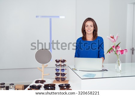 Attractive Woman at the Cashier Counter with Laptop In a Fashion Store, Smiling at the Camera. - stock photo
