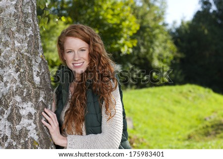 Attractive woman beside a birch tree - stock photo