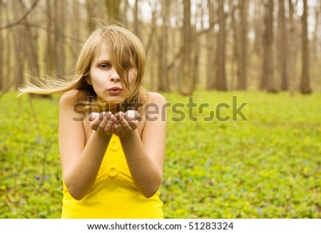 Attractive woman blowing kiss on spring field. Copy space