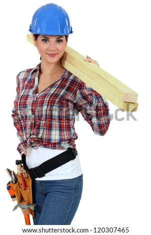 Attractive woman carrying planks of wood - stock photo