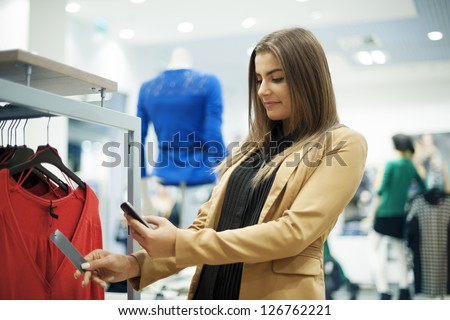 Attractive woman checking bar code in shopping mall - stock photo