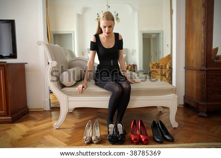 attractive woman choosing a pair of shoes - stock photo