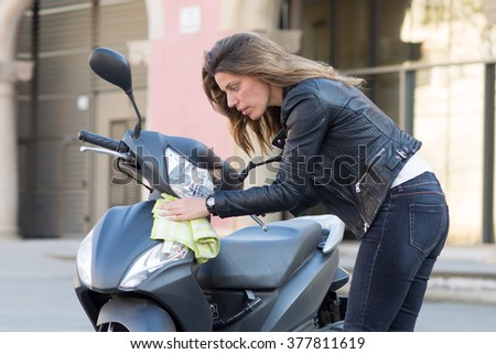 Attractive woman cleans motorcycle - stock photo