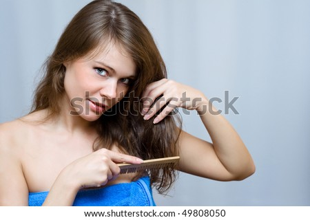 Attractive woman combing her hair - stock photo