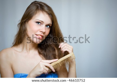 Attractive woman combing her hair by wooden hairbrush - stock photo