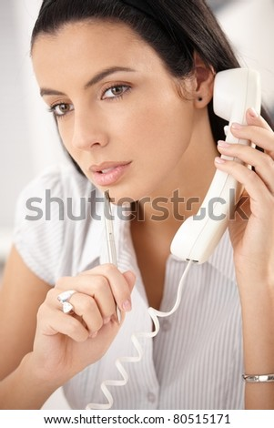 Attractive woman concentrating on landline phone call, thinking, holding pen.?