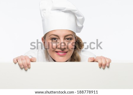 Attractive woman cook smiling behind card board - stock photo