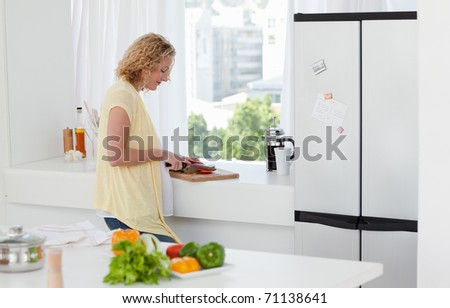 Attractive woman cooking at home - stock photo