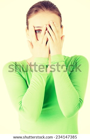 Attractive woman covering her face with both hands. Isolated on white. - stock photo