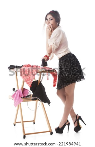 Attractive Woman Covering Mouth While Ironing Clothes Over White Background - stock photo