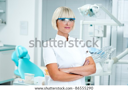 attractive woman dentist standing in her office - stock photo