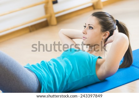 Attractive woman doing abs workout at gym for muscle toning and flat stomach.