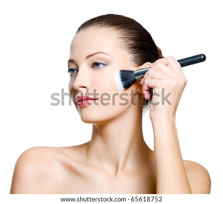 Attractive  woman doing make-up on face. Fashion model posing on white background - stock photo