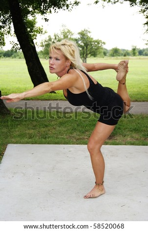 Attractive Woman doing yoga at park - stock photo