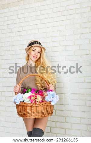 Attractive woman dressed in a sweater and cap holding a basket of flowers. Girl smiling, standing at a brick wall. The concept of innocent beauty. - stock photo