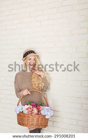Attractive woman dressed in a sweater and cap holding a basket of flowers. The concept of innocent beauty. - stock photo