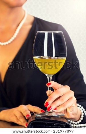 Attractive woman dressed in black sitting at the table and drinking white wine. - stock photo